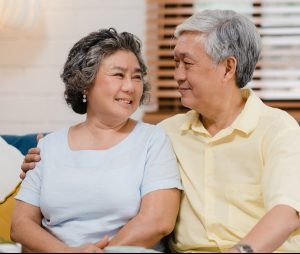 Asian elderly couple holding their hands while taking together i
